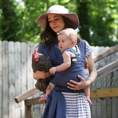 Lady carries a chicken in one arm & baby in a Boba Wrap Vintage Blue
