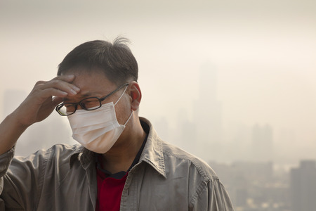Man using a disposable mask having headache because of haze