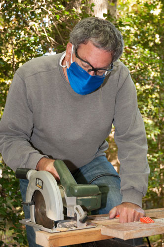 Man using a BreatheHealthy Honeycomb face mask doing wood works