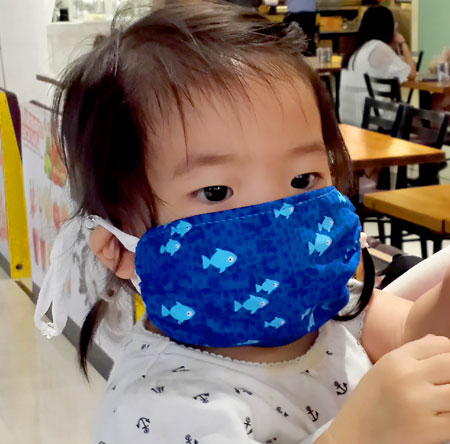 Toddler wearing a Breathe Healthy Reusable Anti Microbial Face mask fish design
